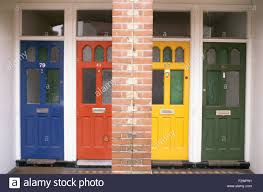 row of colourfully painted front doors on victorian terrace stock