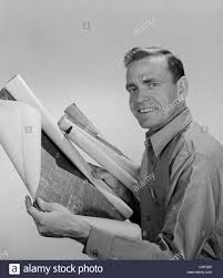 1950s 1960s smiling man builder contractor holding blueprints