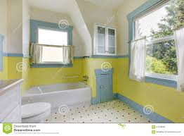 bathroom with yellow walls white tile floor and full bath stock
