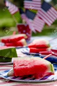 plates that stick to table fresh watermelon slices on a stick sitting on striped plates stock
