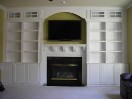 modern white wooden bookshelves and fireplace combined wall