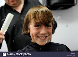 haircuts for 11 year old boys 11 year old caucasian boy having a haircut in a barbers shop in