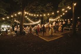 diy backyard wedding in the woods reception string lights rug