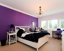 dark purple accent wall with black comforter and classic white bed