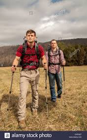 two hikers with backpacks and walking sticks walking to the