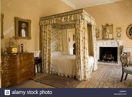 floral drapes and canopy on four poster bed in country house
