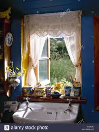 white voile curtains with lace pelmet on window above basin in
