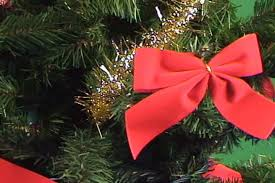 christmas tree with white lights and red bows close up of traditional red christmas bow on decorated with baubles