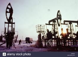 nonworking maintenance worker walks away from non working oil derricks in