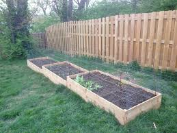 raised garden bed against fence home outdoor decoration