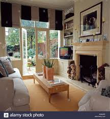 wide striped black white blinds on french windows with view of