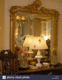 up of large ornate antique mirror above shelf with lighted