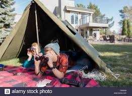 brothers with binoculars in backyard tent stock photo royalty
