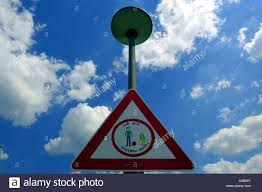 slow down red triangle road sign traffic calming measures blue sky