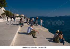 people listening to zadar sea organ croatia stock photo royalty