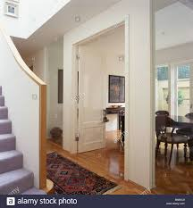open double doors to dining room in open plan modern white hall