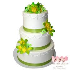 1470 3 tier white wedding cake with green flowers and ribbon