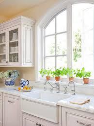 light yellow kitchen with white cabinets windowsill herb garden traditional kitchen bhg