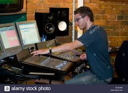 Studio Console Desk by Young Man Mixing At Sound Desk Console Mixer In Recording Studio