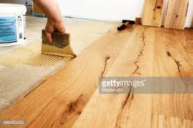 applying glue for laying finished parquet flooring closeup