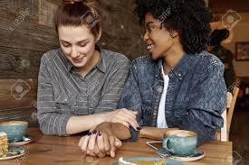 Interacial Lesbians - interracial happy lesbian couple relaxing at cafe redhead