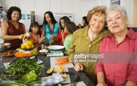 multigenerational hispanic family cooking in kitchen stock photo