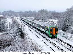 electric trains in snow in arun valley west sussex uk stock photo