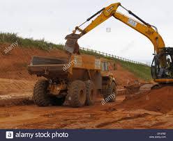 tracked backhoe digger loading large volvo dump truck site tipper