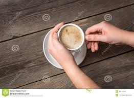 womans hands holding cup of coffee view from top on a warm
