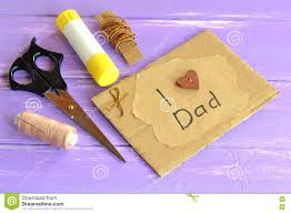 hand greeting card with message i love dad scissors glue cord