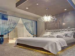 elegant recessed lighting on wooden ceiling design with beautiful chandelier above low king size bed features upholstered tufted velvet headboard