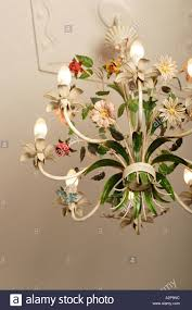 chandelier with floral ornaments hanging from white ceiling stock