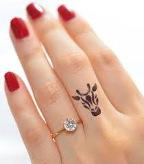 black ink giraffe head tattoo on left hand finger