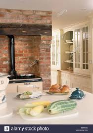 vegetables on table in cottage kitchen with aga oven in exposed
