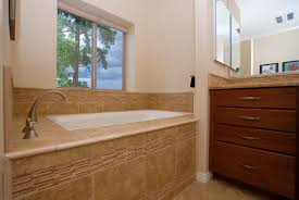 custom home highlights drop in soaker tub with ceramic tile deck and decorative trim