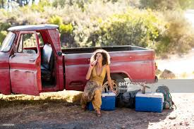 rusty pickup truck young woman sitting next to old rusty pick up truck drinking from