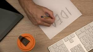 Office Desk Top View Graphic Designer Writing Idea On Piece Of Paper With Felt Pen