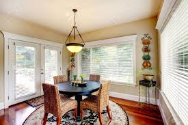 bright room with round dining table and wicker chairs stock photo