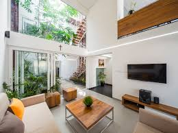 modern living room with a tall ceiling next to a small courtyard