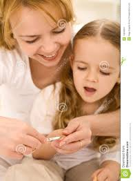 grooming theme woman cuts little girls nails stock images