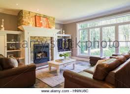 stone fireplace with 2 comfortable chairs in front stock photo