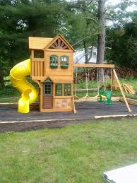 outdoor courtyard with wooden swings and slides yellow then