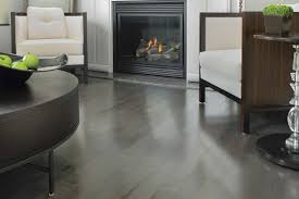 sleek grey hardwood floors to exude maximum modernity traba homes appealing sofas and round table in cozy living area with dark fireplace on grey hardwood floors
