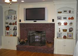 built in bookcase with cabinet around brick fireplace and wall tv