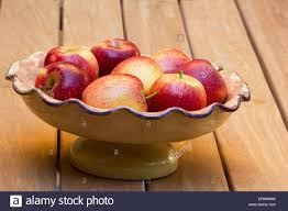 red apples in a fruit bowl on wooden table stock photo royalty