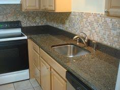 White Cabinets Brown Granite by White Cabinets With Granite Countertops With Patina Paradiso