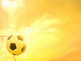 warm yellow football in goal net with warm yellow sky background royalty free