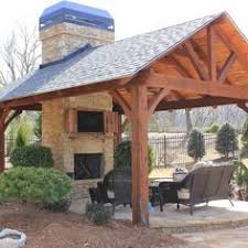 a pavilion with an outdoor kitchen fireplace and an entertainment