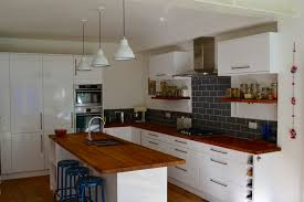 benchmarx white gloss kitchen with oak worktops and grey metro tiles
