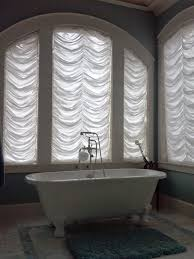 white window treatment for huge arched window in bathroom and old